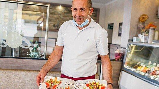 """Robert Berisha zeigt die Karte im Eiscafé """"Orchidea"""" in Zollstock"""