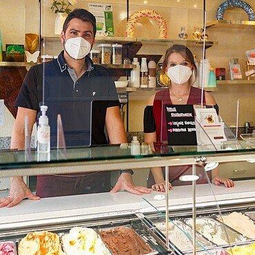 """Daniele Moscetti und Carina Pfahl stehen hinter der Eistheke in der Eisdiele """"Panciera"""" in Brück"""