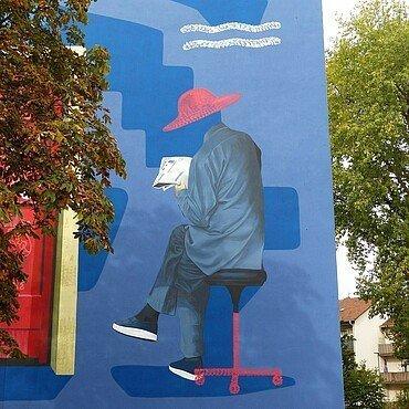 Mural in Müngersdorf zeigt sitzenden Mann aus Hongkong