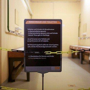 Info-Tafel verkündet: 50 Personen sollten sich eine Toilette teilen