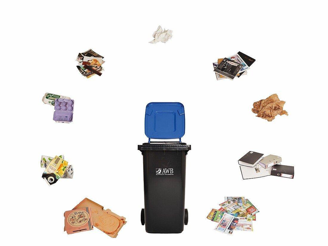 Blaue Tonne umgeben von Müll