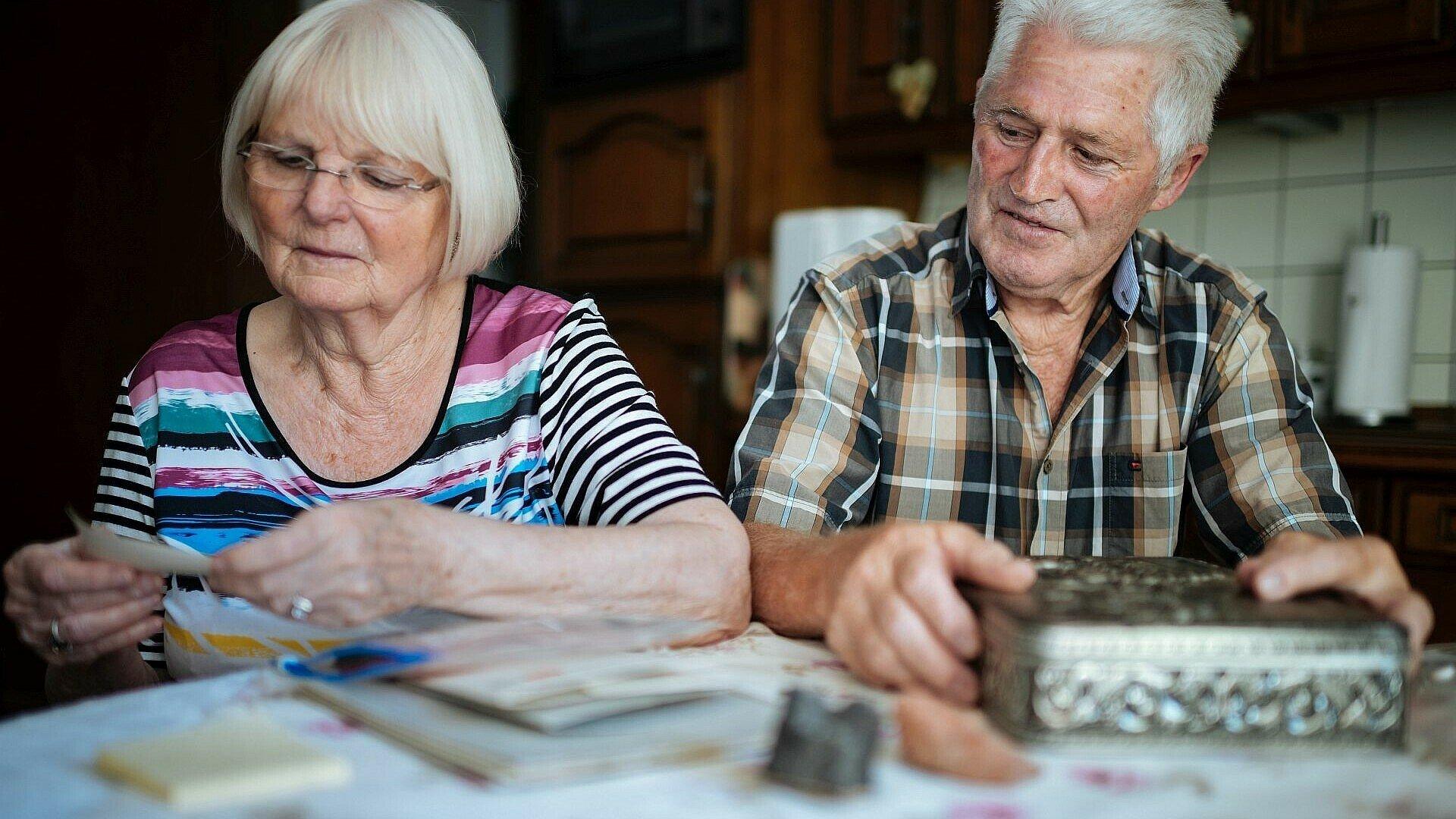 Das Ehepaar schaut sich alte Fotos in ihrer Wohnung in der Rosenhofsiedlung in Bickendorf an