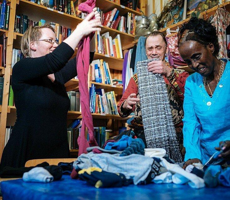 Ehrenamtliche Mitarbeiter sortieren Kleidung im Umsonstladen in Mülheim