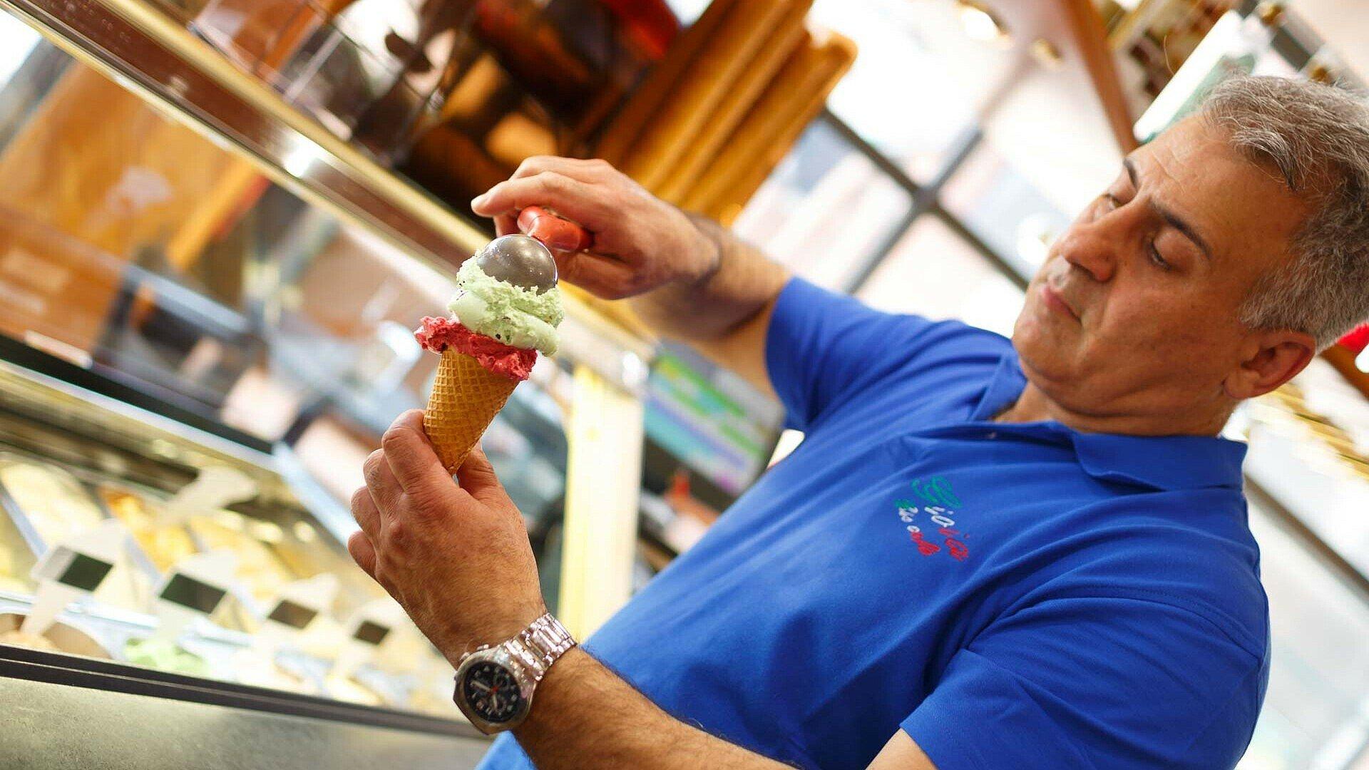 """Giuseppe di Salvo gibt im Eiscafé """"Gioia"""" in Niehl zwei Kugeln Eis in eine Waffel"""