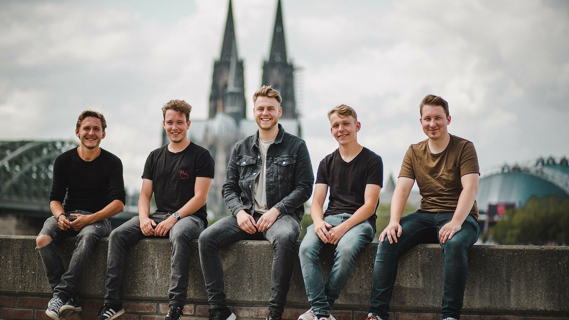 Die Band Zesamm' sitzt am Rheinufer mit Blick auf den Dom