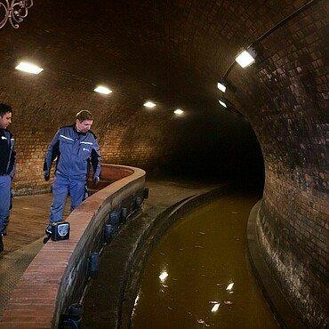 Zwei Mitarbeiter der StEB betrachten das dunkle Dreckwasser im Abwasserkanal