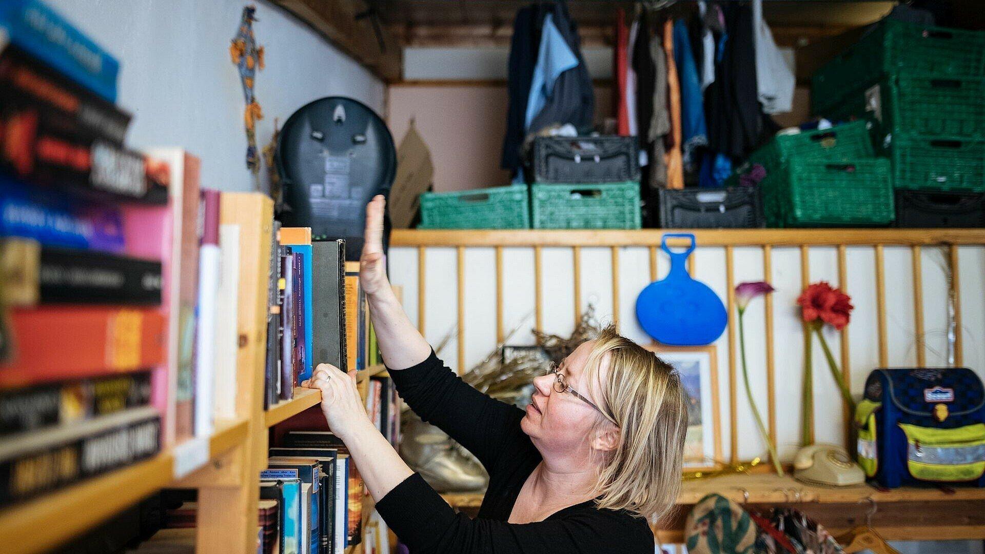 Elisabeth räumt Bücher weg im Umsonstladen in Mülheim