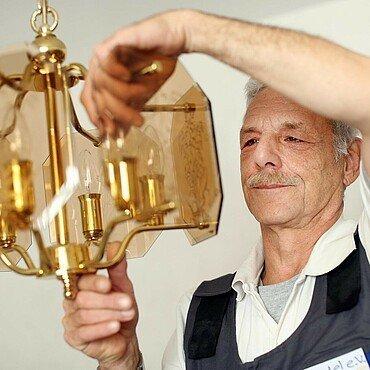 Horst Klug tauscht ein Leuchtmittel aus