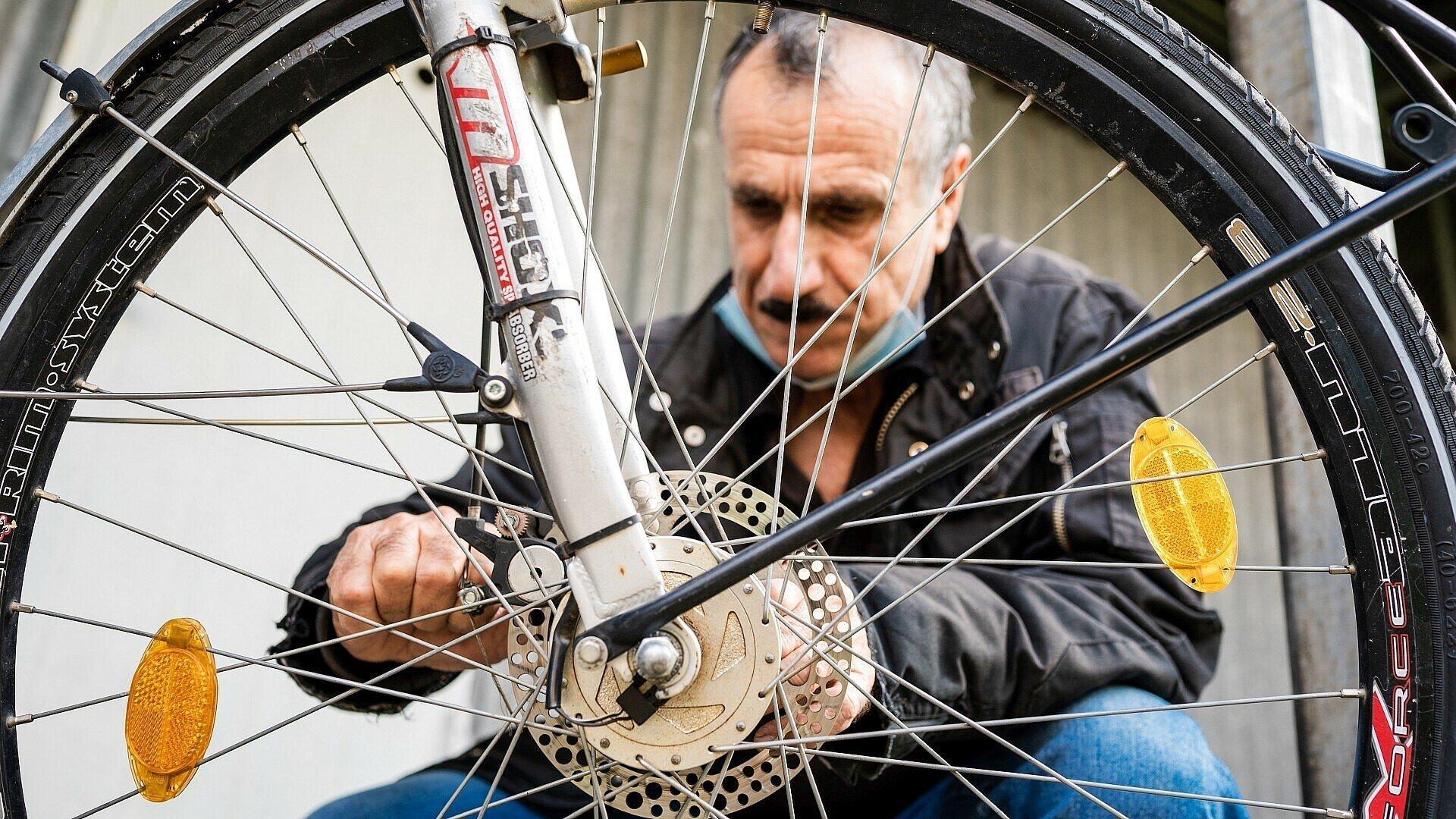 Dakhil schraubt an einem Vorderrad im Bickendorfer Fahrradbüdchen