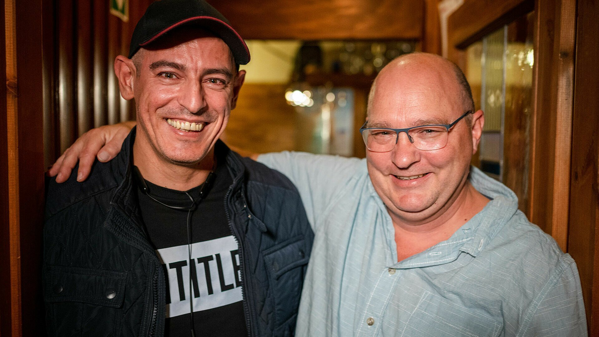 "Murat und Holger lachend Arm in Arm in der Gaststätte ""Vingster Pohl"""