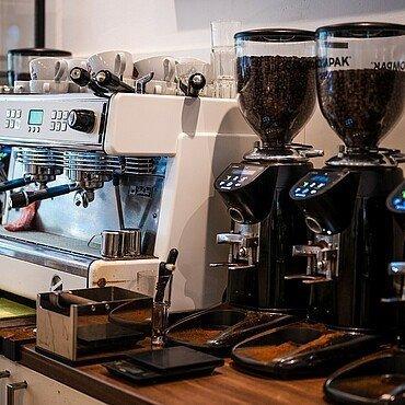 """Siebträgermaschine und Mühlen warten im Café der """"Kölner Kaffeemanufaktur"""" auf ihren Einsatz"""