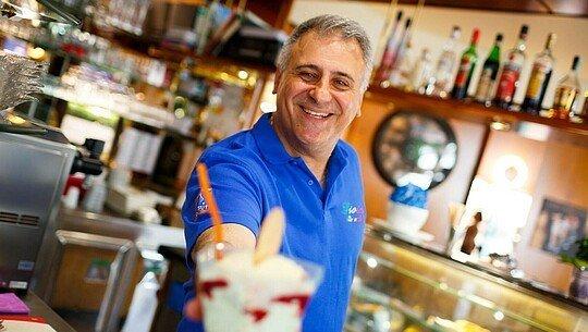 """Giuseppe di Salvo steht im Eiscafé """"Gioia"""" in Niehl und zeigt einen Becher Spaghetti-Eis"""
