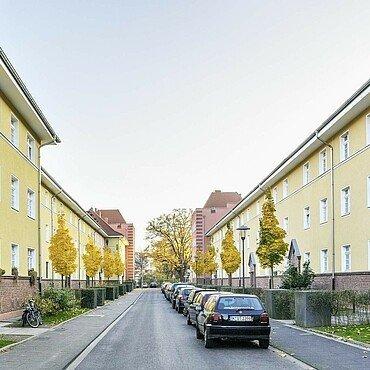 Schmale Straße mit Vorgärten in der modernisierten Germaniasiedlung in Höhenberg