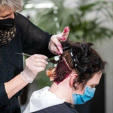 """Petra Keßler trägt Farbe auf die Haare einer Kundin im Friseursalon """"Vivida Nuances"""" in Bocklemünd auf"""