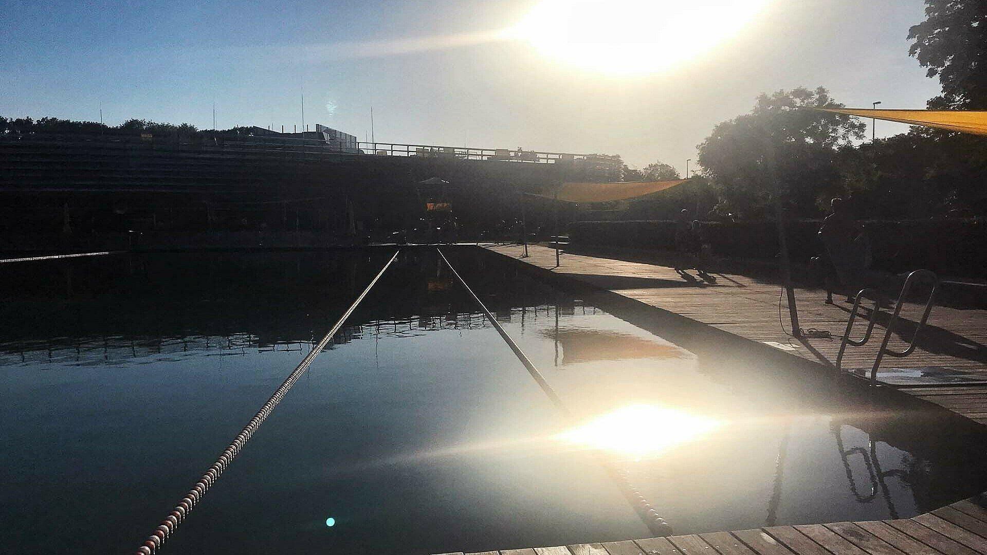 Das Becken des Naturbads Lentpark im Schein des Sonnenuntergangs