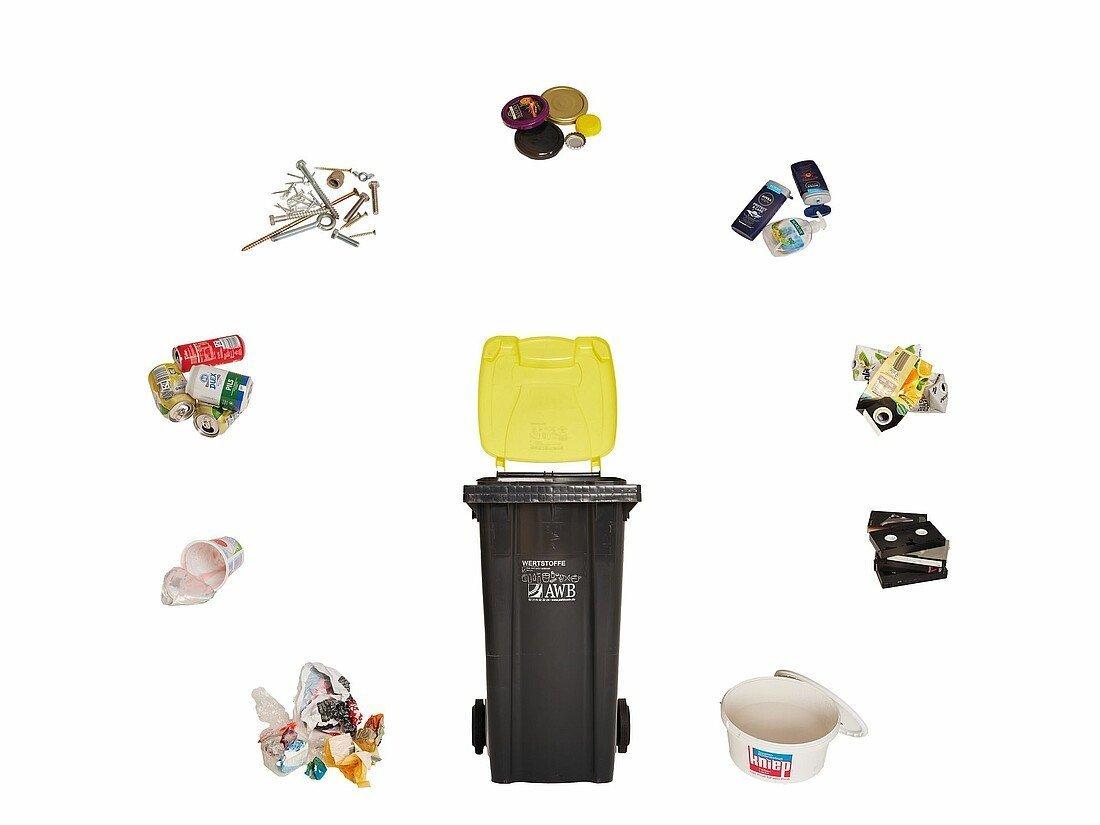 Gelbe Tonne umgeben von Müll