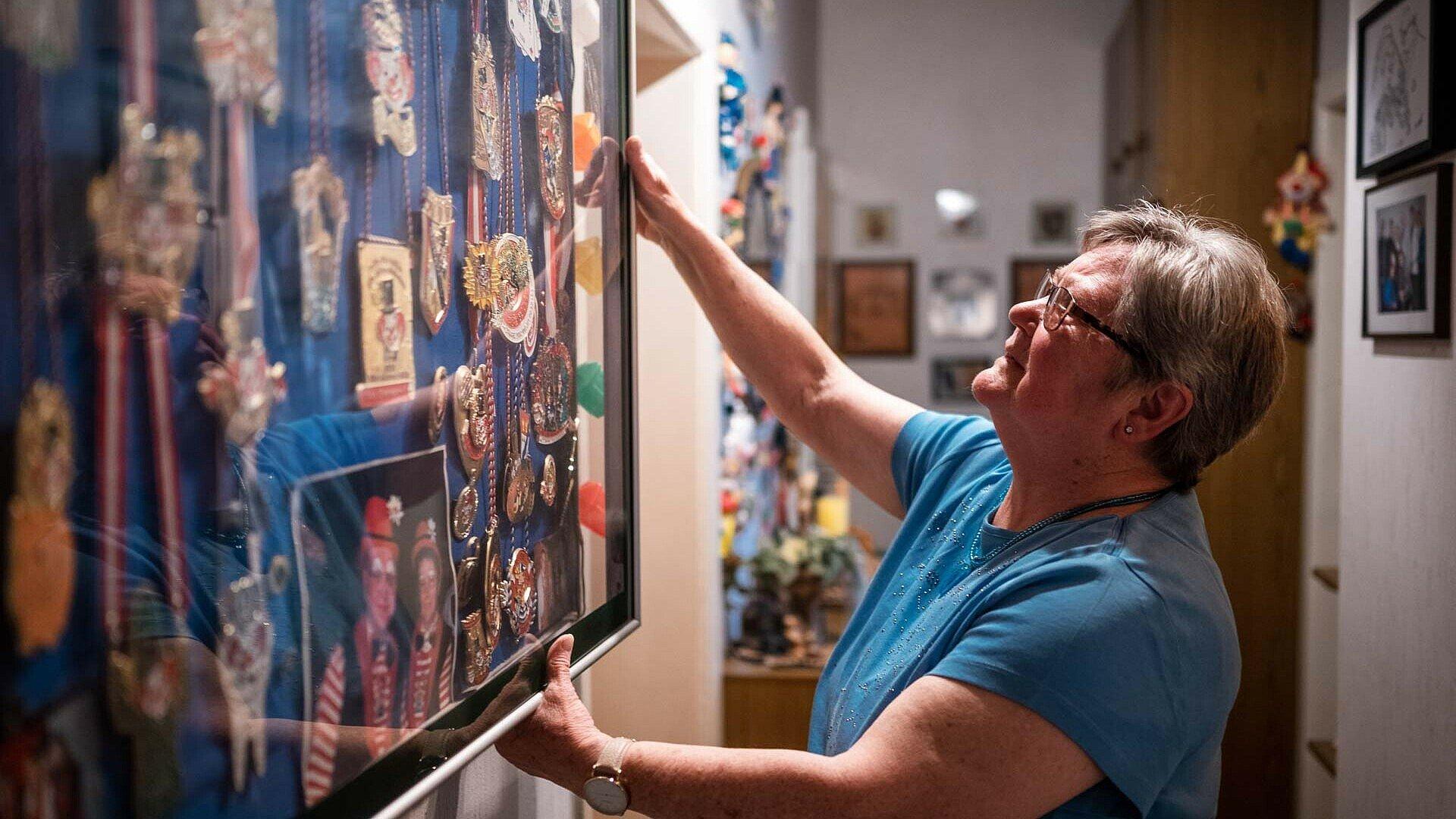 Maria Neubert zeigt den Schaukasten mit ihren Karnevalsorden