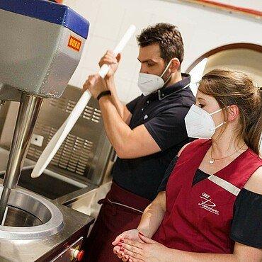 """Daniele an der Eismaschine in der Eisdiele """"Panciera"""" in Brück mit dem langen Spatel, mit dem er das Eis aus dem Zuber holt"""