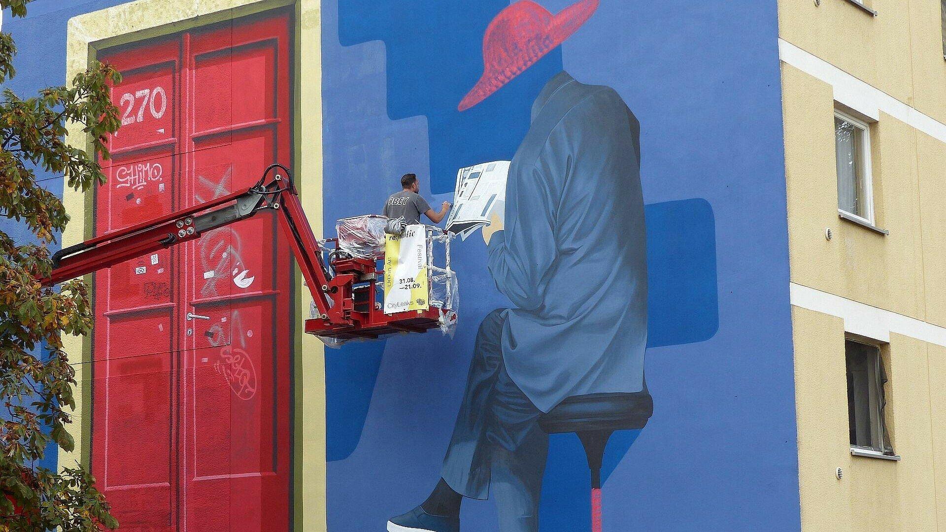 Taroe bei der Arbeit an seinem Mural in Müngersdorf