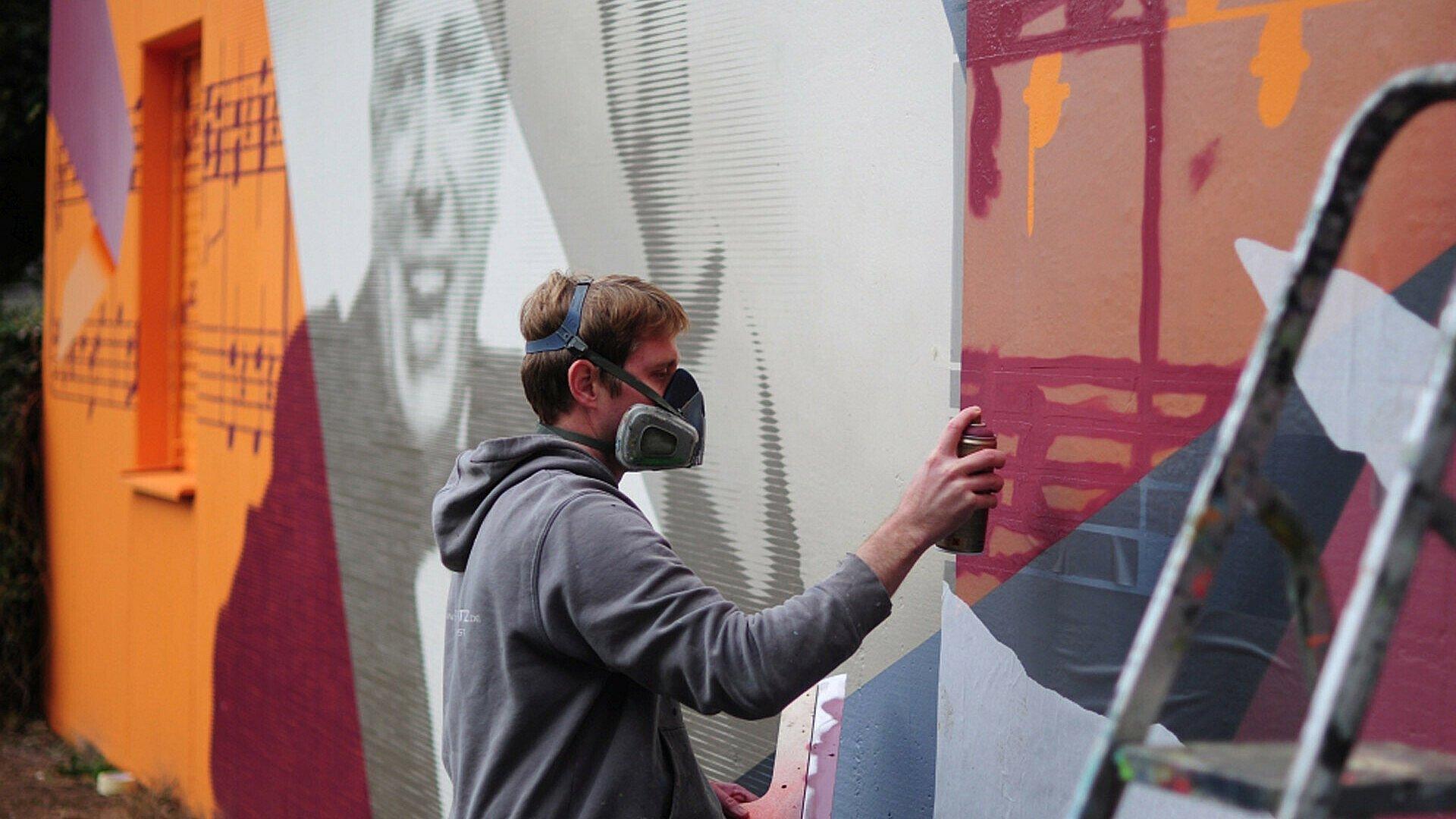 Künstler beim Sprühen des Murals in der Südstadt