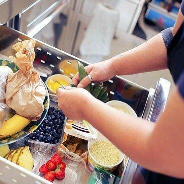 """Mitarbeiterin wählt Zutaten für einen Fruchtbecher im Eiscafé """"Taormina"""" in Dünnwald aus"""