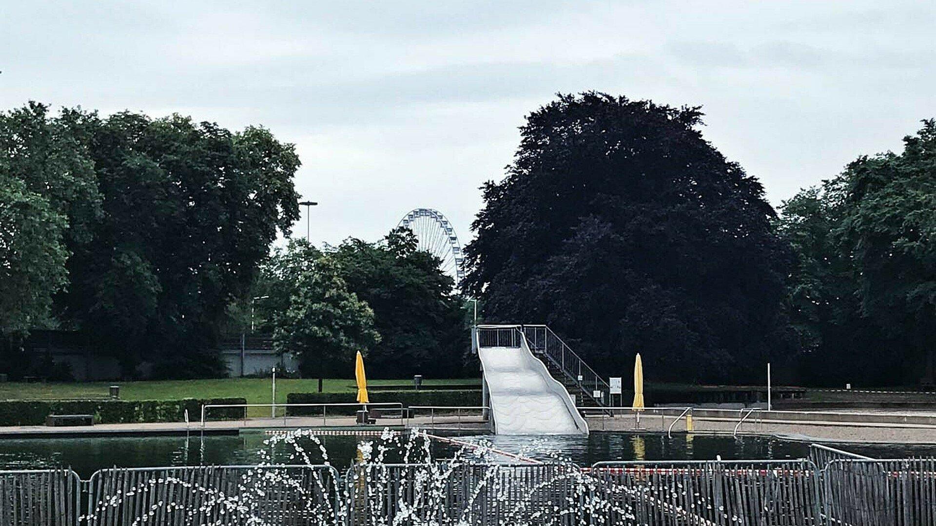 Vom Becken im Lentpark sieht man durch die Bäume das Kölner Riesenrad