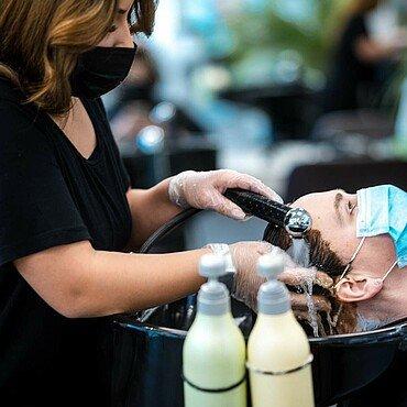 """Eine Mitarbeiterin wäscht die Farbe aus dem Haar einer Kundin im Friseursalon """"Vivida Nuances"""" in Bocklemünd aus"""