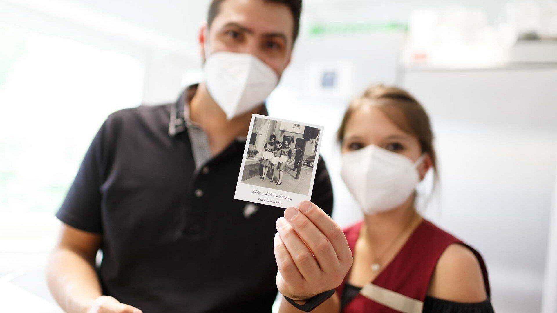 Daniele und Carina zeigen ein historisches Foto