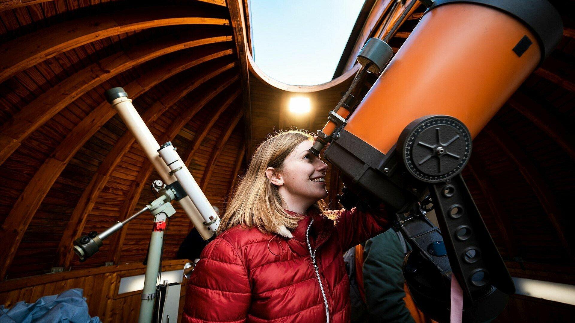 Jana Ruster sieht durch ein Teleskop im Planetarium Nippes