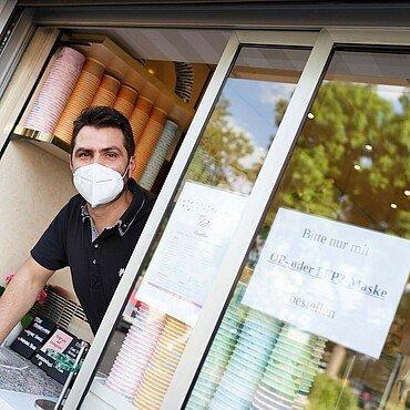 """Daniele schaut aus dem Fenster der Eisdiele """"Panciera"""" in Brück, um die nächste Bestellung aufzunehmen"""