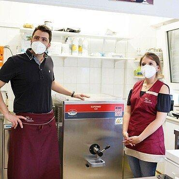 """Daniele und Carina vor der Maschine, mit der Milch und Eier pasteurisiert werden in der Eisdiele """"Panciera"""" in Brück"""