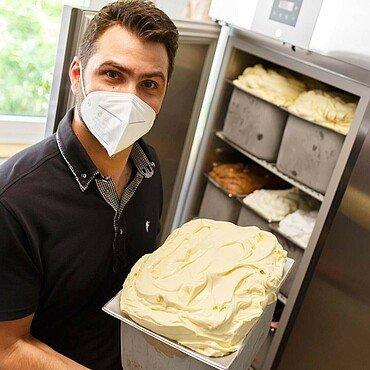 """Daniele zeigt eine große Portion Vanille-Eis in der Eisdiele """"Panciera"""" in Brück"""