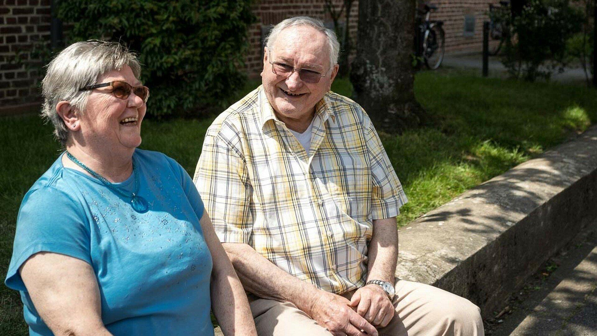 Ehepaar Neubert sitzt lachend in einem Vorgarten der Germaniasiedlung in Höhenberg
