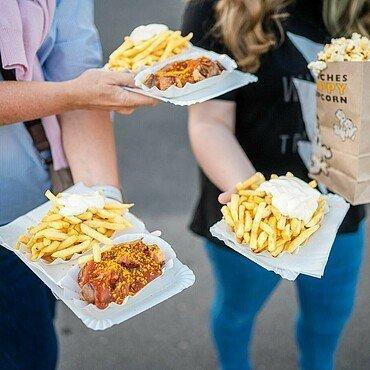 Besucher im Autokino Porz haben sich mit Pommes, Currywurst und Popcorn eingedeckt.