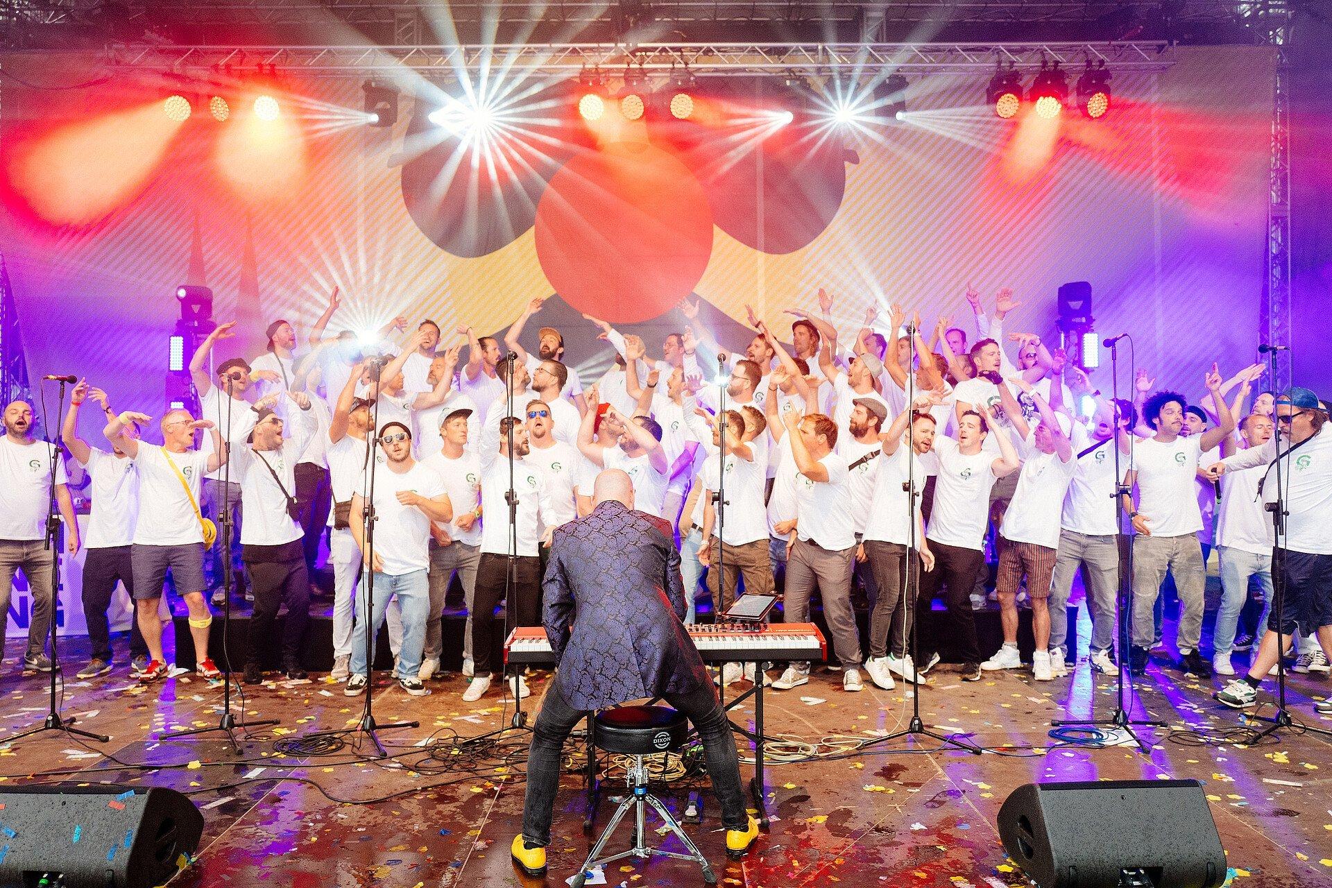 Der Männerchor Grüngürtelrosen steht mit rund 75 Mitgliedern auf einer Bühne