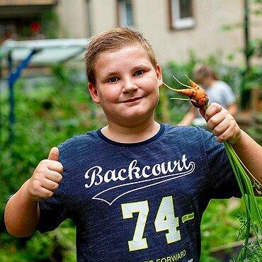 Luca zeigt eine Möhre im GartenClub Bilderstöckchen