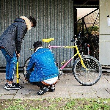 Zwei Jugendliche machen Halt am Bickendorfer Fahrradbüdchen und pumpen ihre Reifen auf