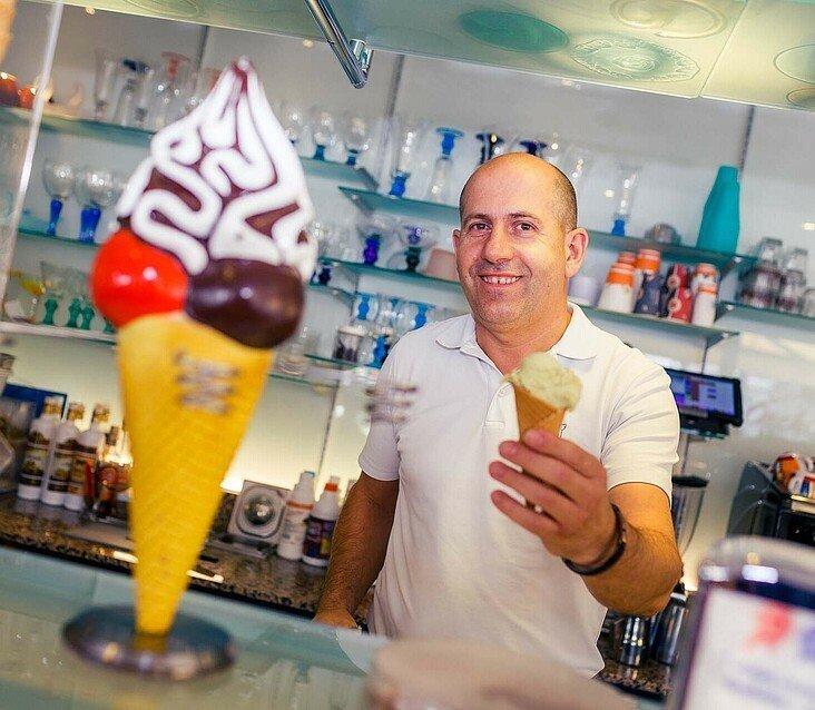 """Robert Berisha präsentiert eine Waffel mit Eis im Eiscafé """"Orchidea"""" in Zollstock"""
