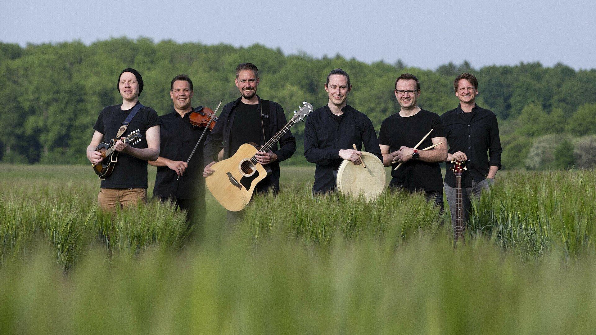 Die Band of plenty steht in einem Feld