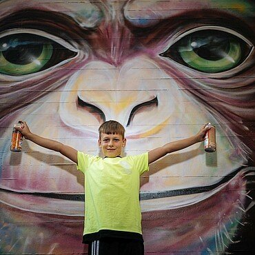 Julian vor einem Motiv der neuen Außenfassade des Jugendzentrums Fzwei.