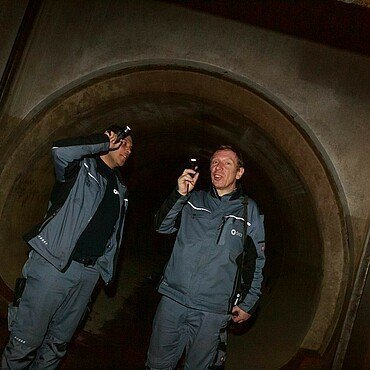 Mit Taschenlampen leuchten zwei Mitarbeiter der StEB die Rohre der Kanalisation aus
