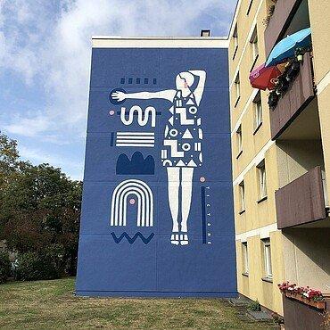 Mural in Müngersdorf zeigt eine Frau mit Kleid aus geometrischen Formen