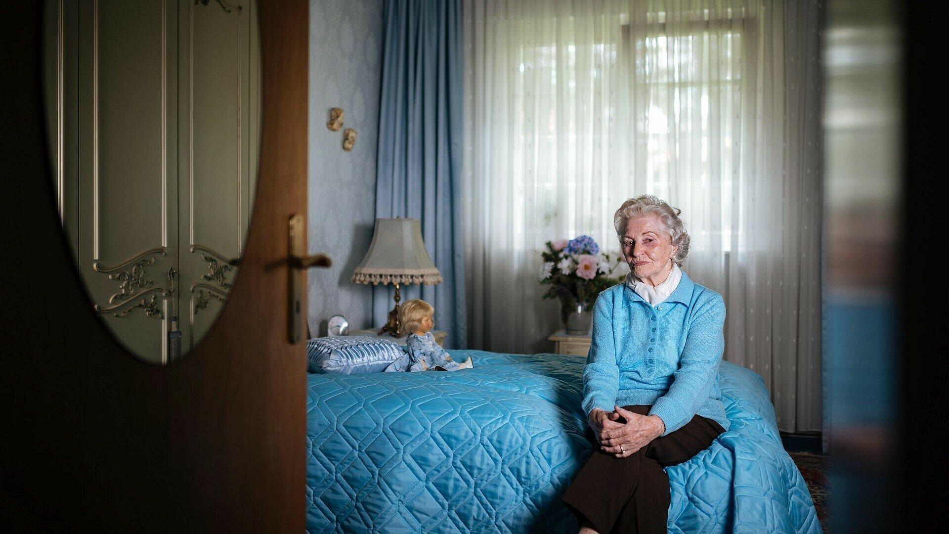 GAG-Mieterin sitzt auf ihrem Bett in der Rosenhofsiedlung.