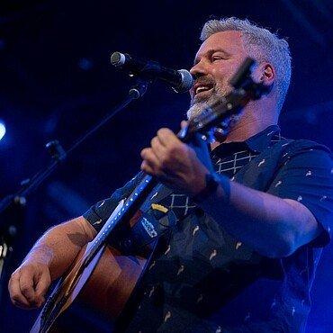 Der Musiker mit seiner Gitarre auf der Bühne