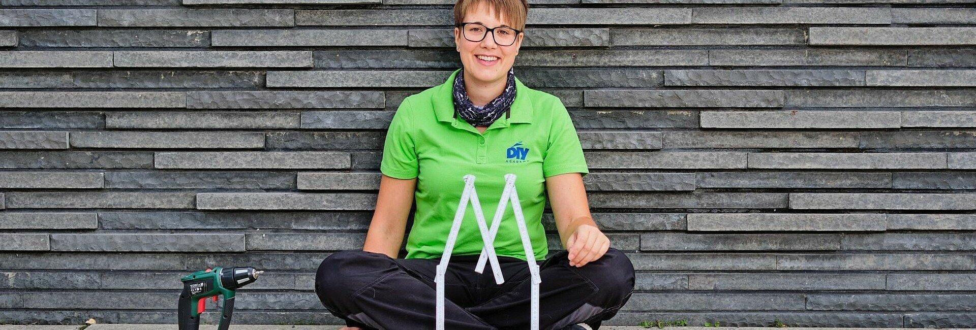Miss DIY Kerstin Weiser sitzt mit Werkzeugen an der Rheinpromenade