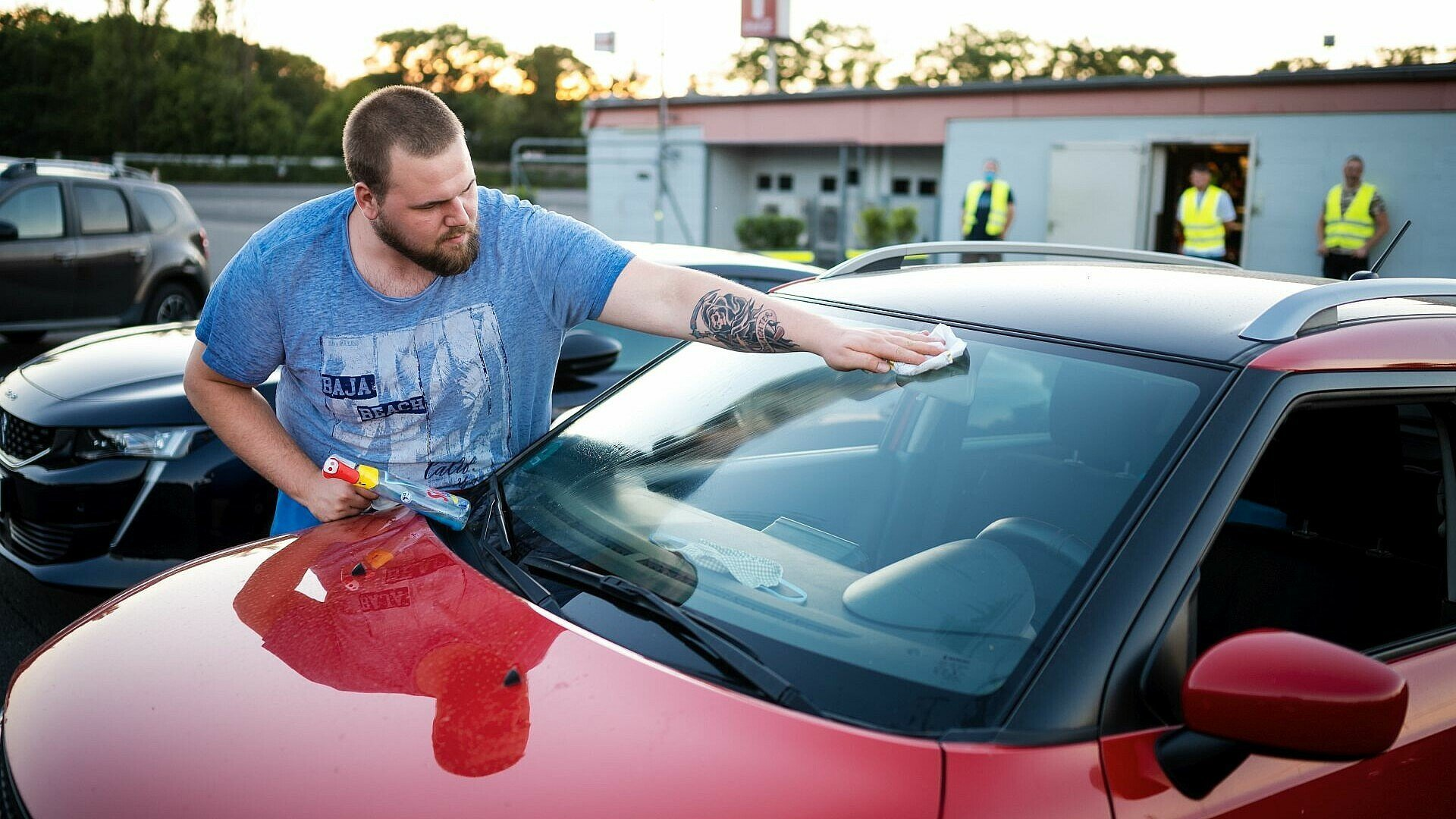 Ein Besucher putzt vor dem Filmstart im Autokino Porz die Windschutz-scheibe seines Autos