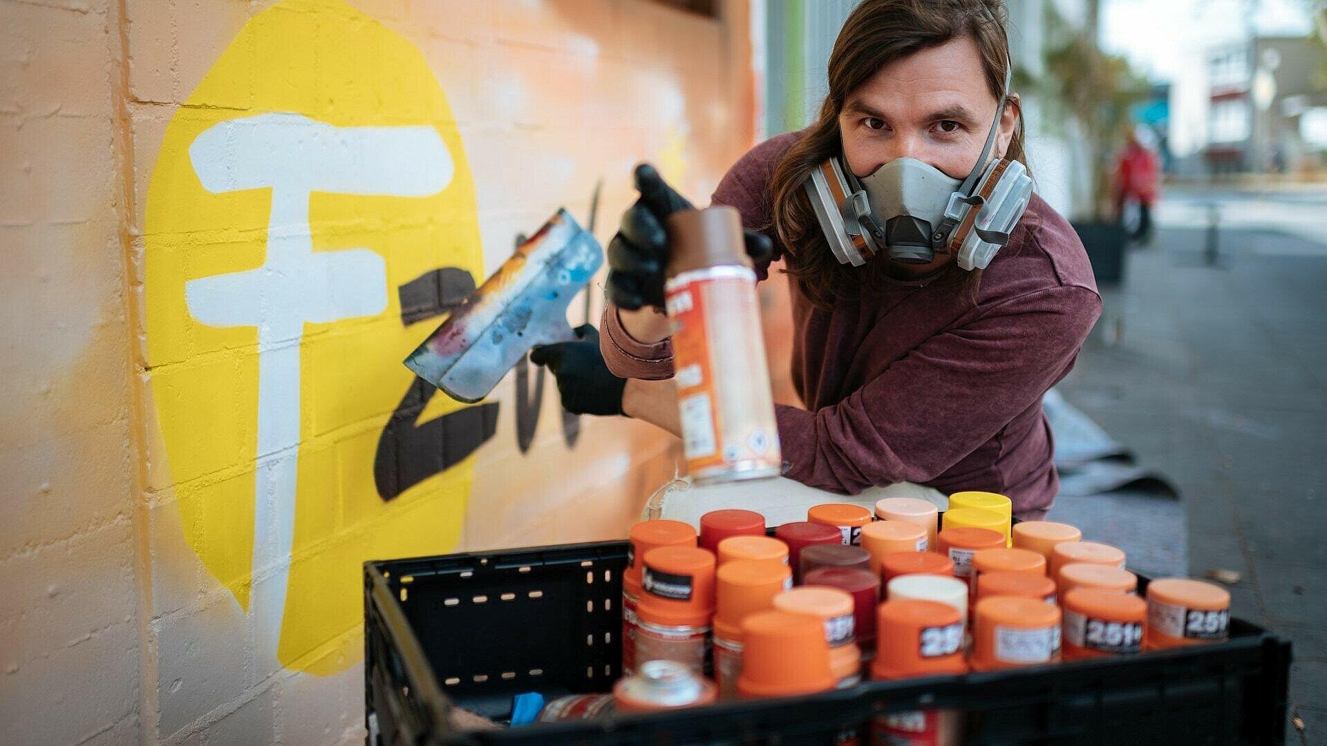 Künstler Matthias Furch sprüht das Logo des Jugendzentrums auf die Wand